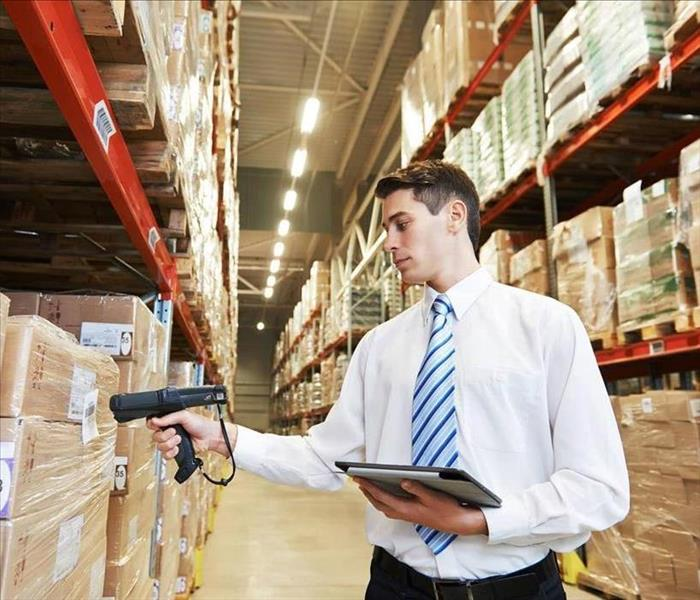 Man scanning inventory in warehouse